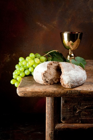 the sacrament: Sacred wine chalice with grapes and holy bread Stock Photo