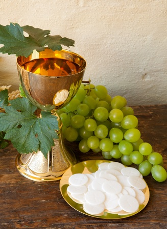 the sacrament: Holy communion image showing a golden chalice with grapes and bread wafers