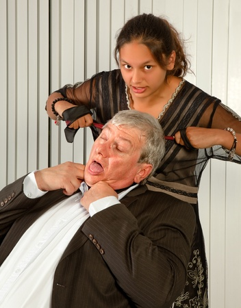 to strangle: Office worker or secretary strangling her boss with his own tie Stock Photo