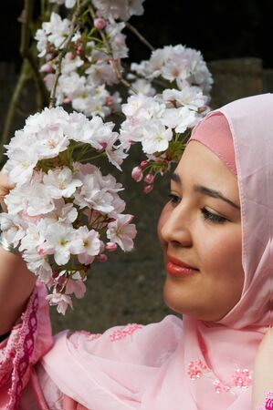 purdah: Young smiling islamic woman admiring blossom flowers in springtime Stock Photo