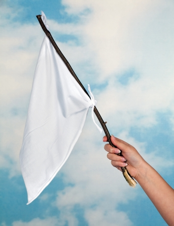 Female hand waving with a white flag to surrender photo
