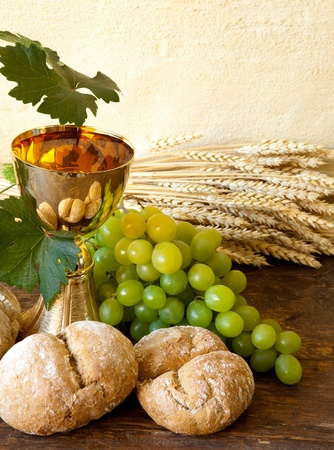 holy jug: Grapes and holy bread next to a golden chalice with wine  Stock Photo