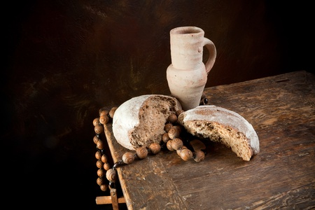 Antique rosary and wine pitcher with a rustic loaf of bread Stock Photo - 8923198