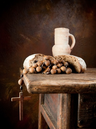 Antique rosary and wine pitcher with a rustic loaf of bread photo
