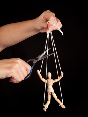 hands off: Hand cutting the strings of a puppet, giving it freedom Stock Photo