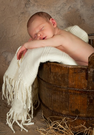 Vintage photo of a newborn baby of 18 days old sleeping in an antique bucket Stock Photo - 9019740