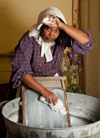 launder: Victoriana Mujer lavando ropa con una tabla de lavar antiguo Foto de archivo
