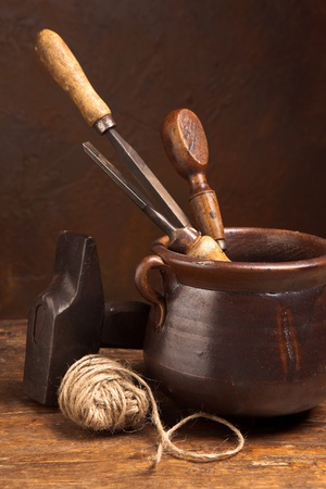 Grunge tools and old rope in a rustic pot photo