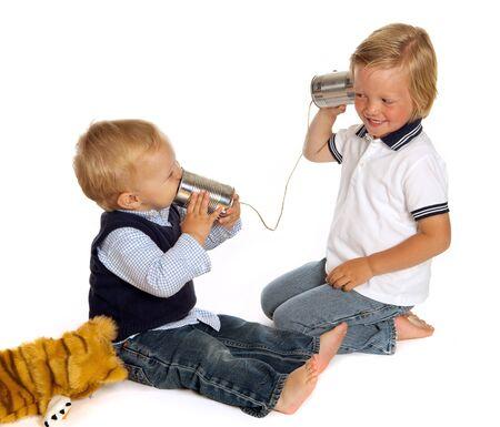 ni�os hablando: Dos hermanitos hablando por tel�fono mediante dos latas y un trozo de cuerda