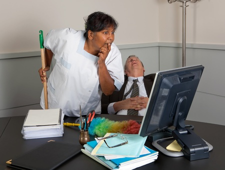 Curious cleaning woman reading the computer while the office manager is sleeping photo