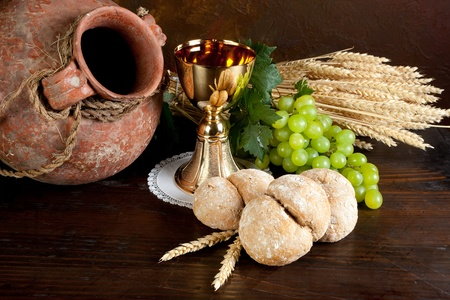 pitcher: Grapes and holy bread next to a golden chalice with wine