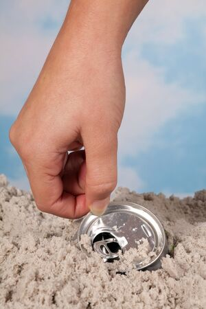Female hand picking up a discarded soda can on a beach Stock Photo - 9172930