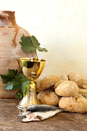 Bread and fish with an antique wine jug symbolizing the miracles of Jesus Christ photo
