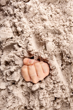 quicksand: Hand or fist on a beach sinking or drowning in quicksand
