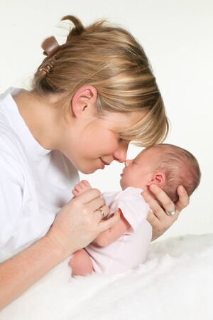 narozený: Young loving mother hugging her sleeping 18 days old baby