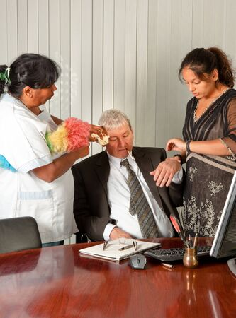 Secretary and cleaning woman taking care of the office manager with a fever Stock Photo - 9279318