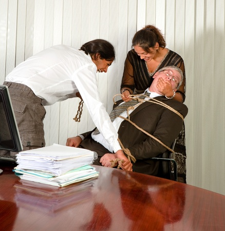 Employees tying the office manager to his chair with a rope photo