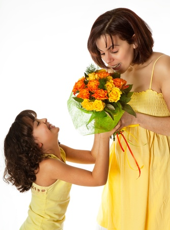 Little girl giving flowers to mom on mothers day photo