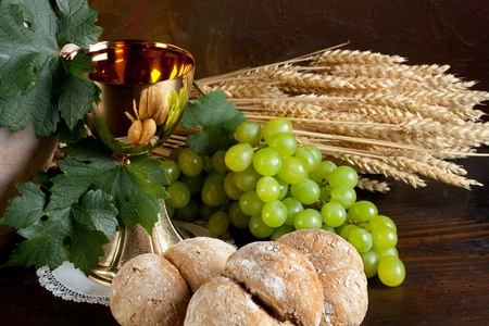 holy jug: Grapes and holy bread next to a golden chalice with wine