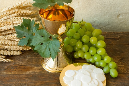 hosts: Holy communion image showing a golden chalice with grapes and bread wafers