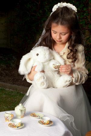Little Alice in Wonderland girl drinking tea with a white rabbit
