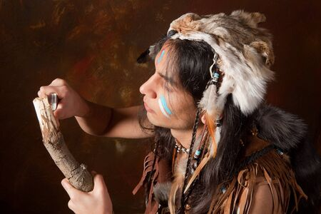 native american man: Portrait of an Indian in traditional costume wearing eagle feathers, coyote fur and beads