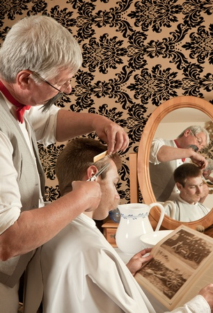 Barber cutting the hair of a customer in an antique victorian barbershop (the antique magazine is from 1910). Stock Photo - 11779333