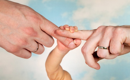 Thee hands of a baby and his parents with wedding rings photo