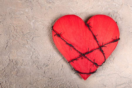 Barebed wire wound around a red heart on a grungy background photo