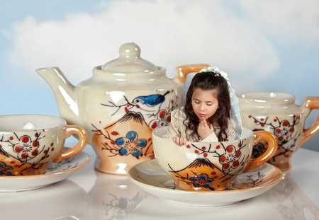 little table: Tea party with antique tea cups and a miniature girl like in alice in wonderland