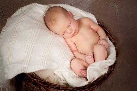naked child: Newborn baby sleeping in an grungy wicker basket