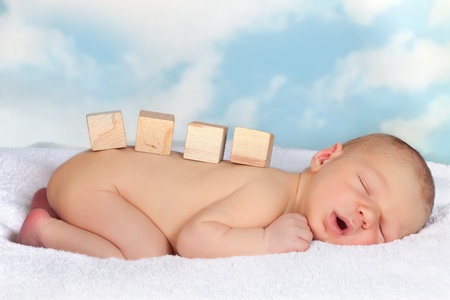 Four empty blank wooden blockx on a naked sleeping baby photo