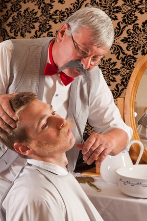 Barber cutting the mustache of a customer in an antique victorian barbershop  photo