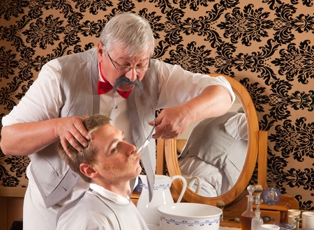 barber chair: Barber cutting the mustache of a customer in an antique victorian barbershop