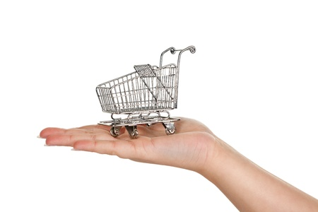 Female hand carrying a miniature shopping trolley photo