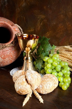Grapes and holy bread next to a golden chalice with wine Stock Photo - 9646143