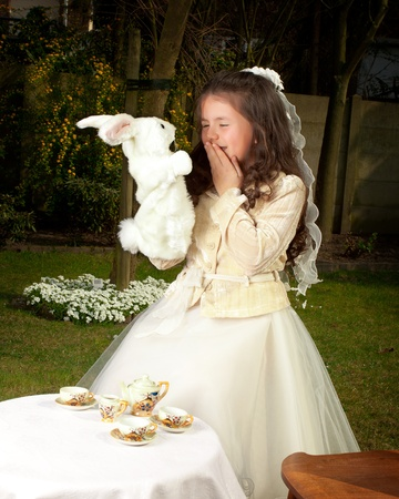Alice in Wonderland girl drinking tea with a white rabbit