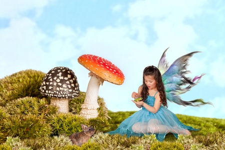 Little fairy girl with wings putting a crown on a green tree frog photo