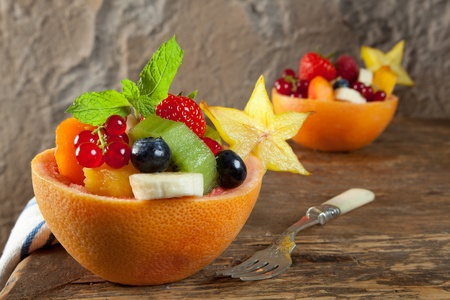 Two portions of fruit salad in grapefruit bowls on an antique table photo