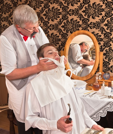 barbershop: Victorian barber finishing the shave of a customer (the antique magazine is from 1910).