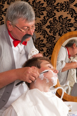 barbershop: Antique barber shaving a customer with shaving cream
