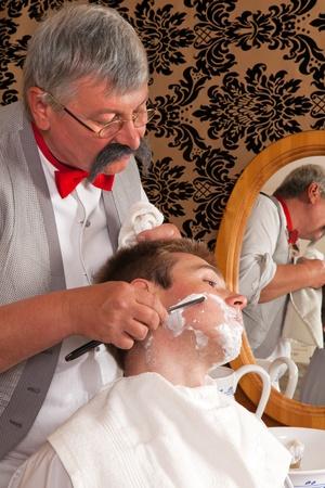 peluquerias: Barbero antiguo afeitado a un cliente con crema de afeitar Foto de archivo