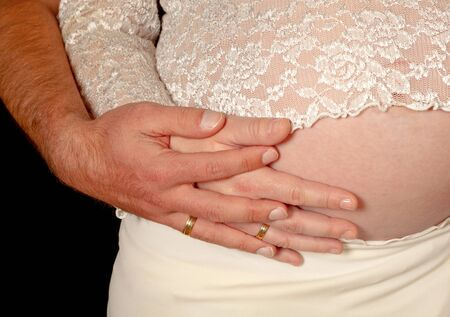 Hands with wedding rings of a couple on a pregnant belly Stock Photo - 9776739