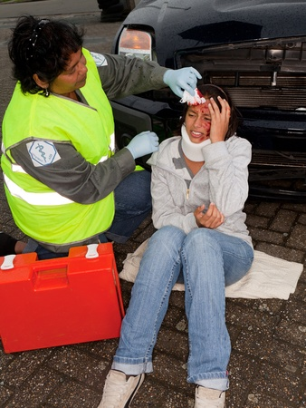 Female paramedic attending to a young car crash victim (the sleeve badges have been replaced by a non existing logo) photo