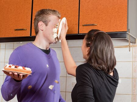Young woman putting a cream pie in her boyfriend's face