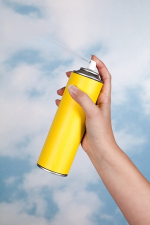 Hand spraying a substance like insecticide into open air Stock Photo
