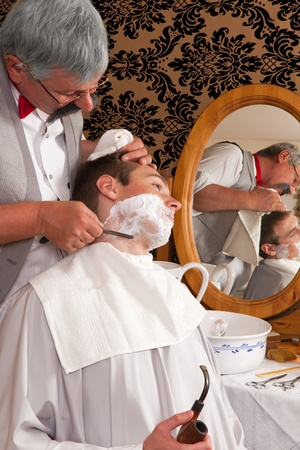 Antique barber shaving a customer the old-fashioned way photo