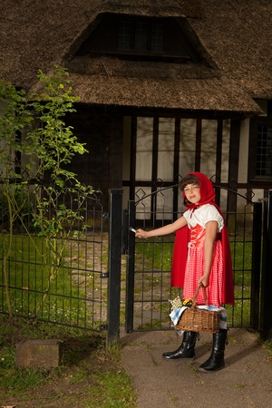 Little red riding hood opening the gate the her grandmother's cottage photo