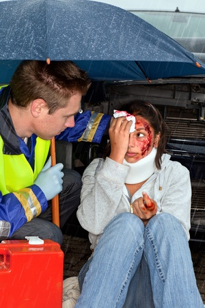 accident patient: Injured woman being cared for in the rain