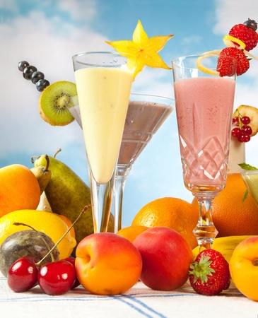 smoothies: Batidos de fruta color pastel sobre un fondo de cielo azul